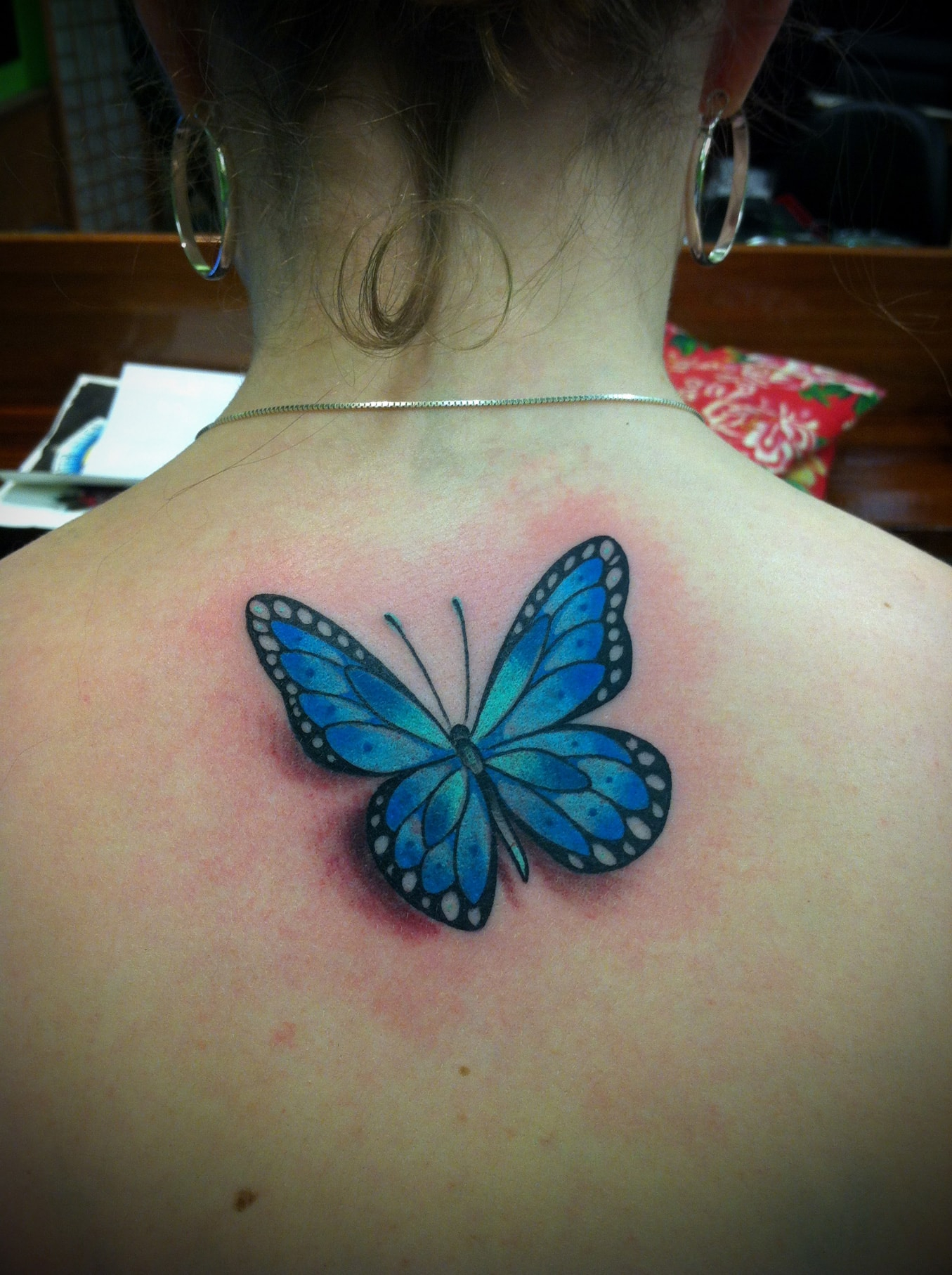 Blue Ink Butterfly Tattoo On Girl Upper Back in measurements 1355 X 1814