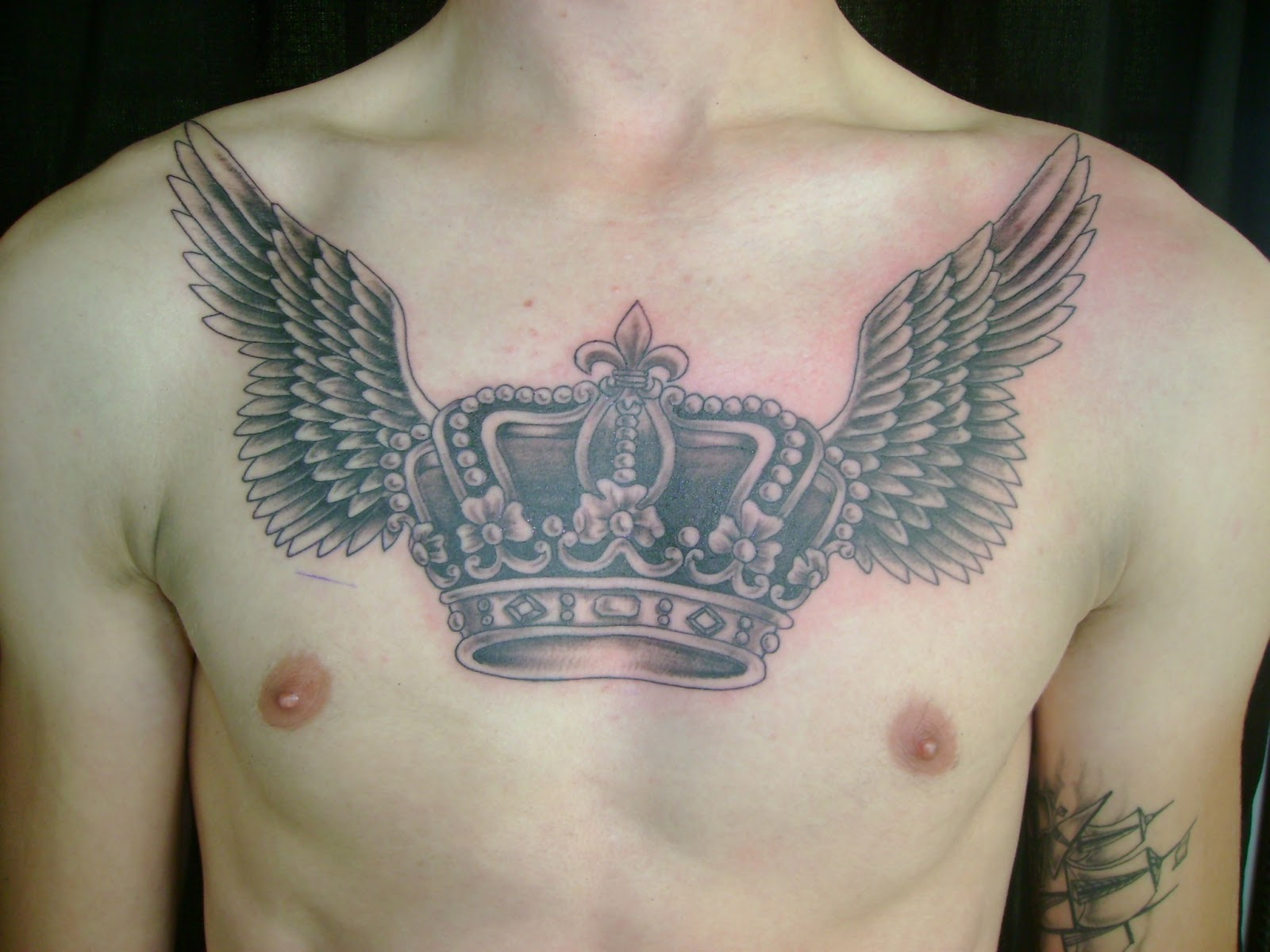 Grey Ink Winged Crown Tattoo On Man Chest for proportions 1600 X 1200